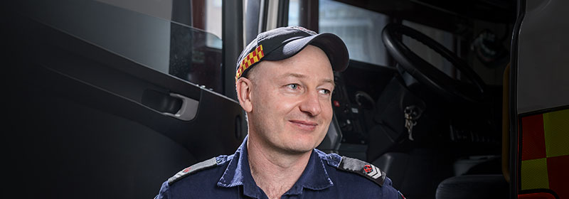 An emergency services worker with a small smile looking off camera and 2019 World's Most Ethical evaluation badge.