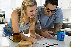 Man and woman at home in kitchen looking over a bill
