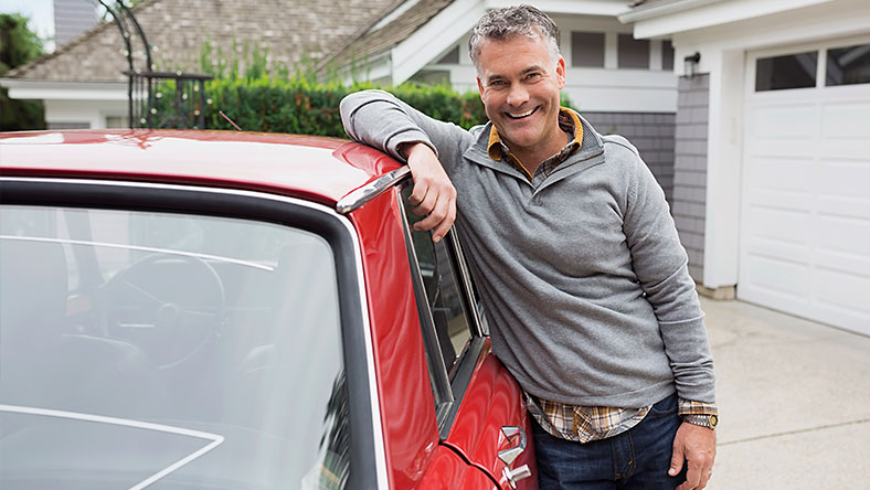 Grey haired man leaning against the window of a red car parked in suburban driveway