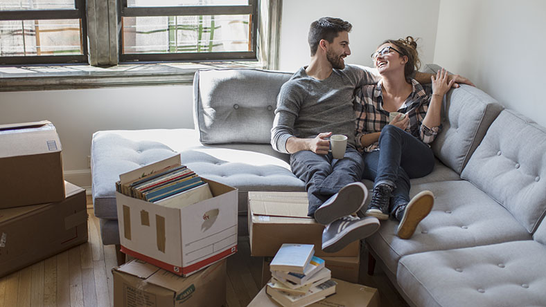 Couple relaxing on couch while moving into new home